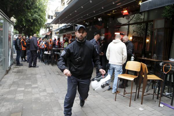 Image: Israeli policemen runs at the scene of a shooting incident in Tel Aviv, Israel