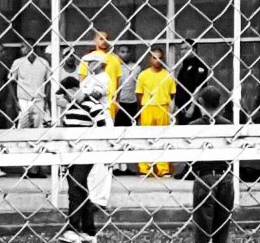 Venezuelan activists Francisco Marquez, left, and Miguel San Miguel, right, in yellow, stand outside the July 26 prison in San Juan de los Morros, Venezuela