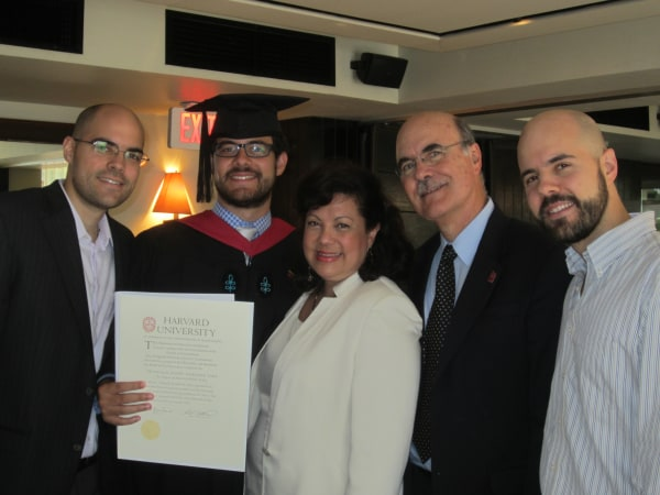Venezuelan activist and lawyer Francisco Marquez, surrounded by his family, holds his diploma after graduating from Harvard's John F. Kennedy School of Government