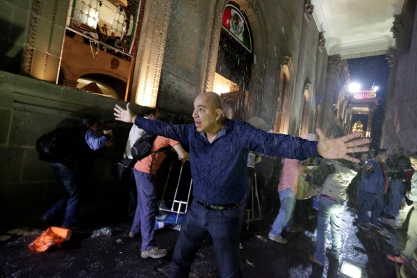 Image: Man urges fellow demonstrators to calm down as they vandalise the Government Palace