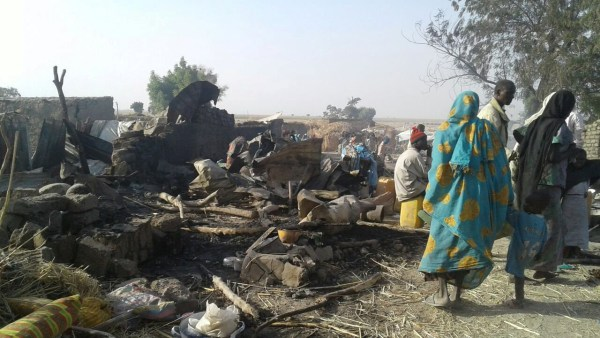 Image: People walk at the site after a bombing attack of an internally displaced persons camp in Rann