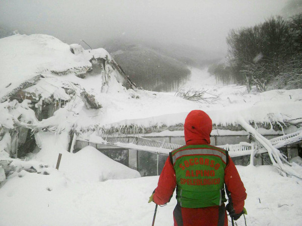 Image: A rescuer stands in front of the Hotel Rigopiano in Farindola, Italy