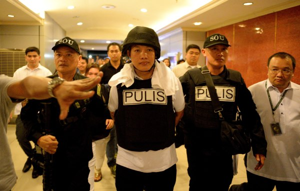 Image: Police officer Ricky Sta. Isabel (C), one of the suspects in the kidnapping and murder of South Korean businessman Jee Ick Joo, is escorted by fellow policemen as they leave the National Bureau of Investigation building in Manila on Jan. 20, 2017.