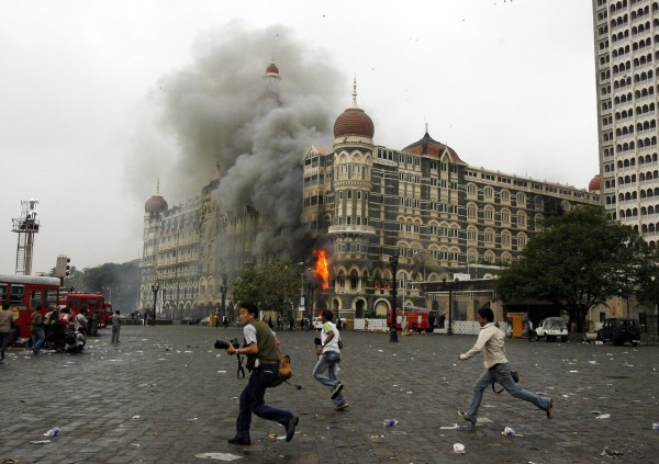 Image: Photographers run past a burning Taj Mahal Hotel during a gun battle in Mumbai