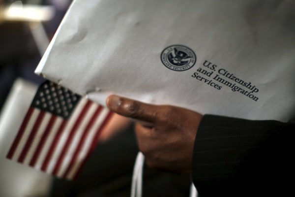 Image: A man holds an envelope from the U.S. Citizenship and Immigrations Service during a naturalization ceremony at the National Archives Museum in Washington