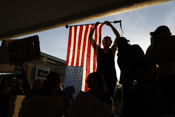 Image: A demonstrator holds an American flag during a rally at SFO