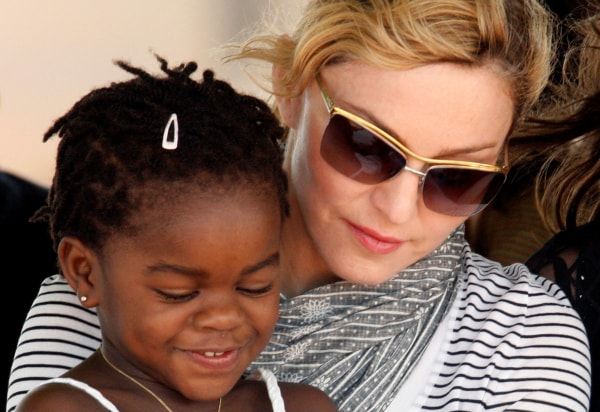 Image: FILE PHOTO: Madonna sits with her adopted Malawian child Mercy James during a bricklaying ceremony at the site of her Raising Malawi Girls Academy