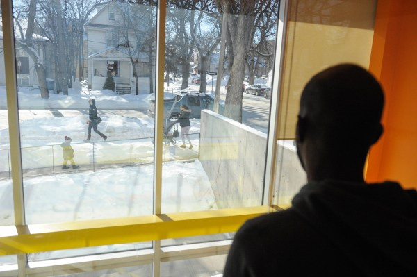 Image: A refugee claimant from Djibouti looks out the window of the Manitoba Interfaith Immigration Council shelter
