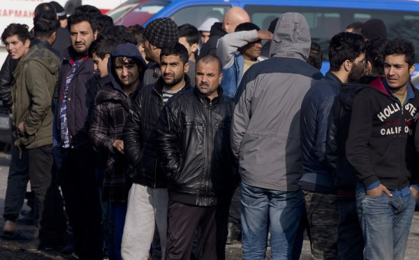 Image: Migrants line up to buy food