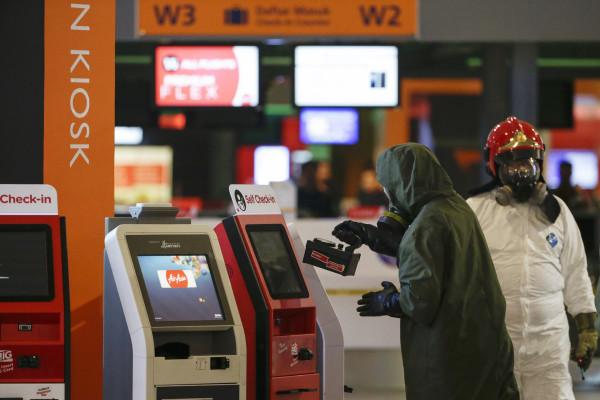 Image: A hazmat team conducts checks in Kuala Lumpur International Airport