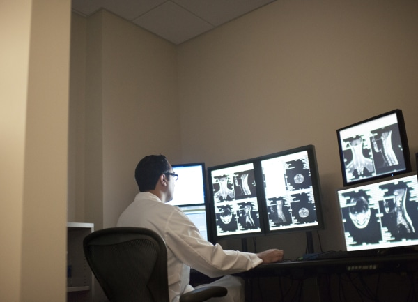 Radiologist checks X rays on multiple computer scr