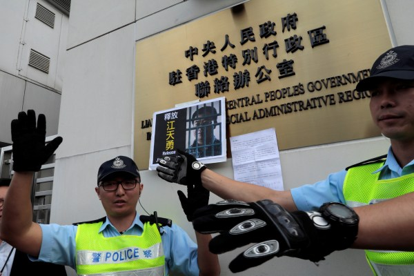 Image: Police react in front of disbarred lawyer Jiang Tianyong's portrait