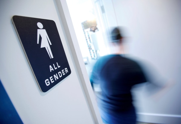 Image: FILE PHOTO - A bathroom sign welcomes both genders at the Cacao Cinnamon coffee shop in Durham North Carolina