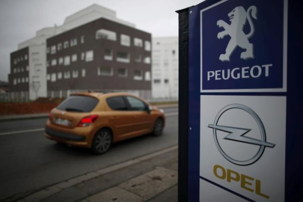 A Peugeot car drives past the logos of French car maker Peugeot and German car maker Opel at a dealership in Villepinte