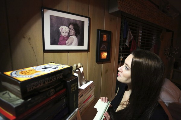 (Casey Anthony looks up at a portrait of her with her daughter)