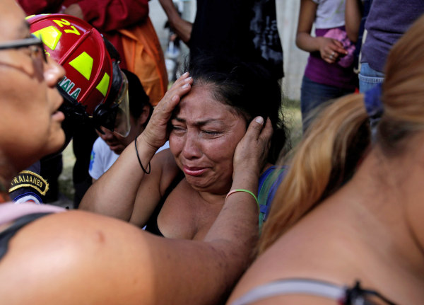 Image: Family members react as they wait for news of their loved ones after a fire broke at the Virgen de Asuncion home in San Jose Pinula