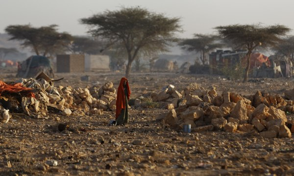 Image: A Somali woman walks through a camp of people displaced from their homes