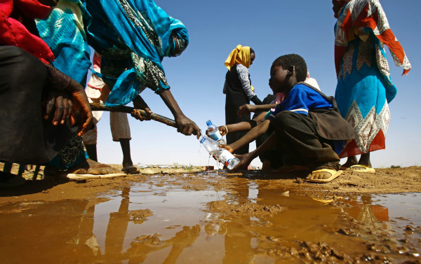 Image: A Sudanese woman fills water bottles
