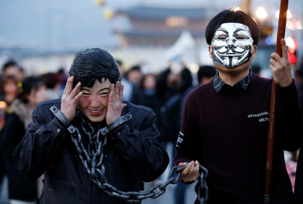 Image: A protester in a mask depicting South Korea's ousted leader Park Geun-hye wears shackles at a rally against Park in Seoul