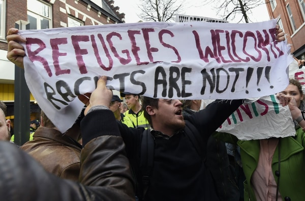 """Image: A protester with a banner reading """"Refugees welcome, racists are"""