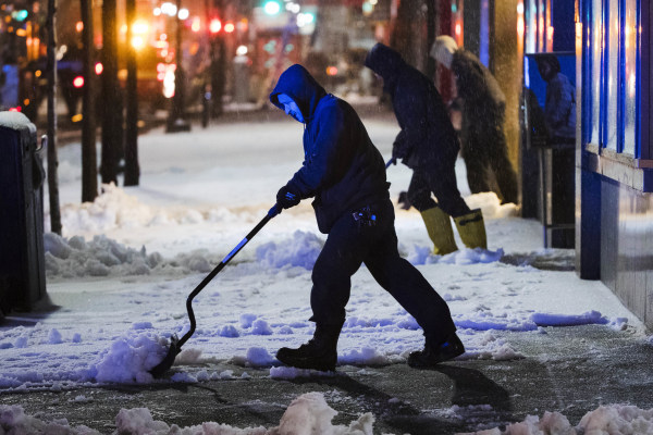 Image: Workmen clear a sidewalk during a winter storm in Philadelphia