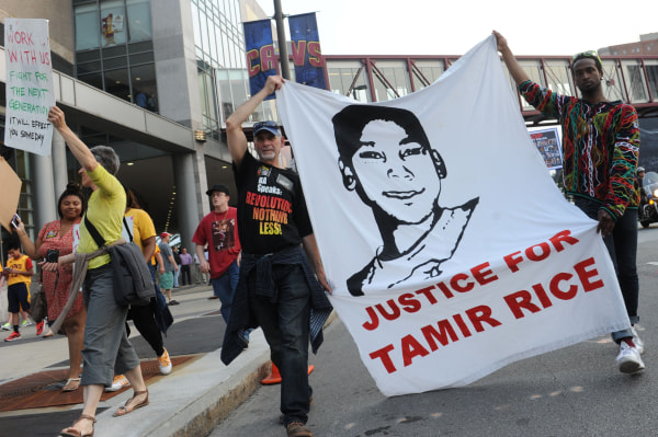 Image: Demonstrators hold signs in support of Tamir Rice outside of Quicken Loans Arena before to game three of the NBA Finals