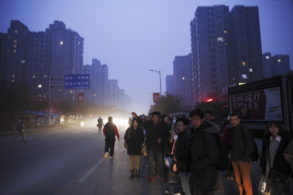 Image: People wait for a bus to Beijing