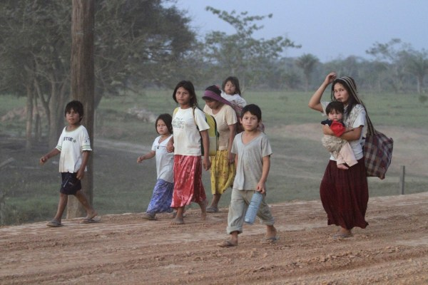 Image: Tsimane indigenous people walk down a road heading to Yucomo, Bolivia
