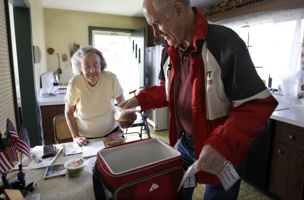 Image: Marty Robertson unpacks food from the Chagrin Falls Meals on Wheels program for recipient Bernadette Winko, 90, in her Bentleyville, Ohio home on Wednesday, March 14, 2012.