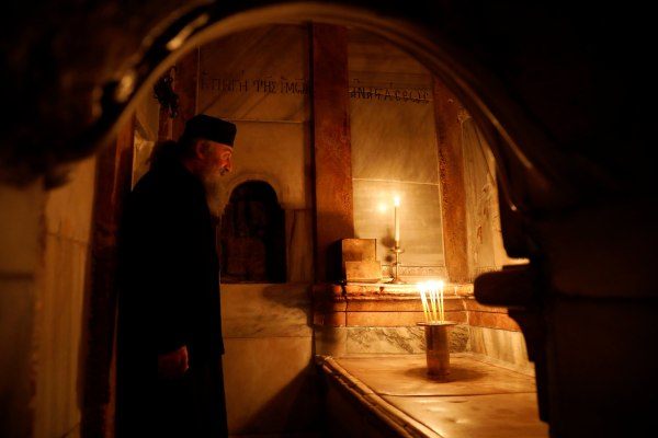 Image: A Greek Orthodox priest stands inside the newly restored Edicule at the Church of the Holy Sepulchre in Jerusalem's Old City