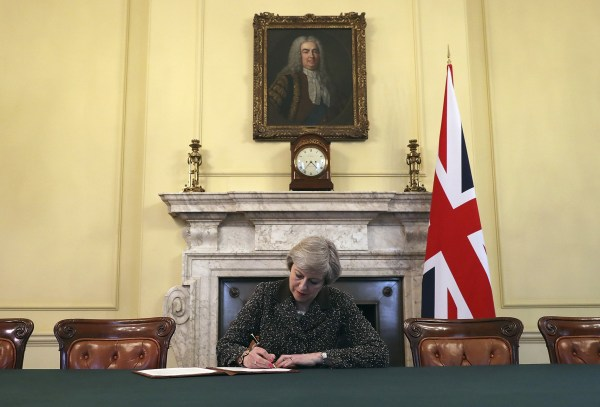 Image: Britain's Prime Minister Theresa May signs the official letter to European Council President Donald Tusk