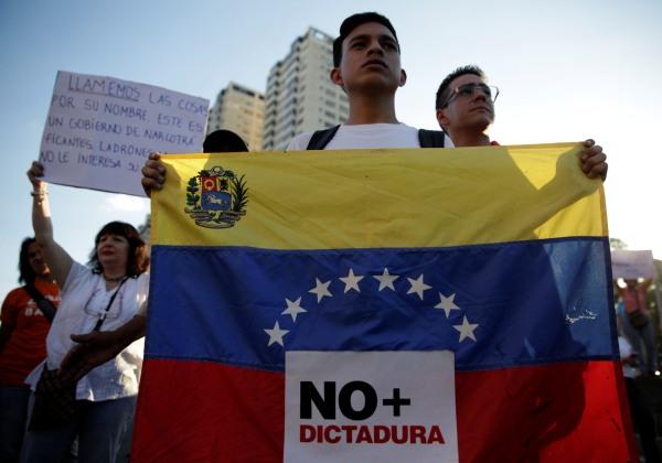 "Image: An opposition supporter holds a Venezuelan flag with a sign that reads ""No more dictatorship"" during a protest against Venezuelan President Nicolas Maduro's government, in Caracas"