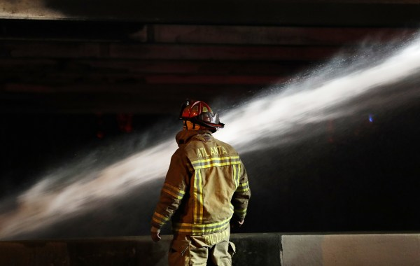 Image: A firefighter surveys the section of an overpass that collapsed from a large fire on Interstate 85 in Atlanta on March 30, 2017