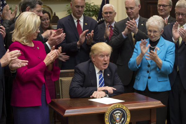 Image: President Donald Trump, flanked by Reps. Liz Cheney (R-Wyo.) and Virginia Foxx (R-N.C.), signs a series of bills during a ceremony in the Roosevelt Room of the White House in Washington.
