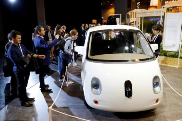 Visitors look at a self-driving car by Google displayed at the Viva Technology event in Paris