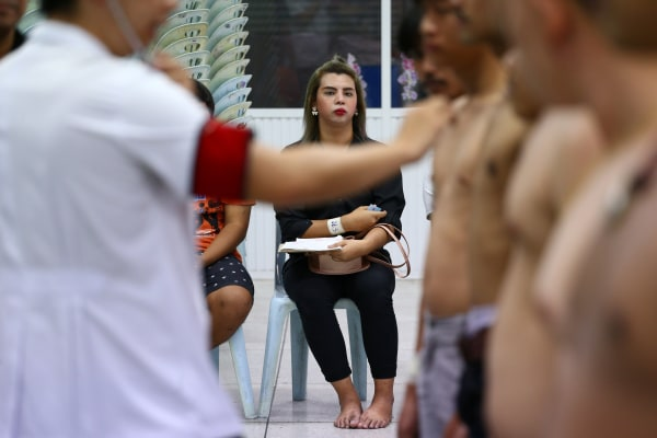 Image: A transgender waits for a health examination during an army draft held at a school in Klong Toey, the dockside slum area in Bangkok