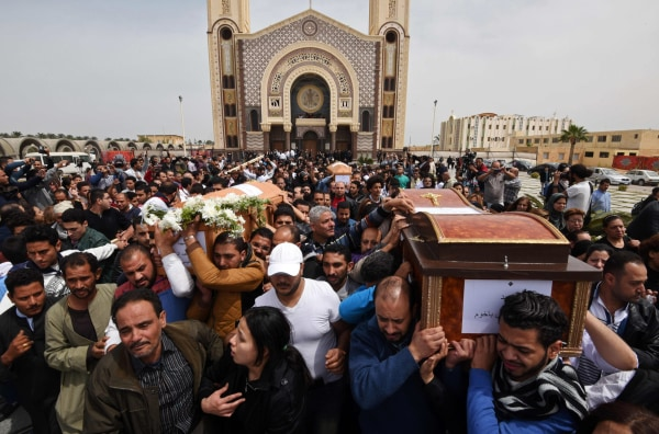 Image: Mourners carry the coffins of victims of a bomb at a Coptic church in Alexandria