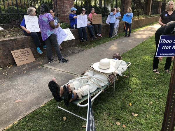Image: Judge Wendell Griffen portrays a prisoner on a gurney during a protest against executions in front of the Governor's Mansion