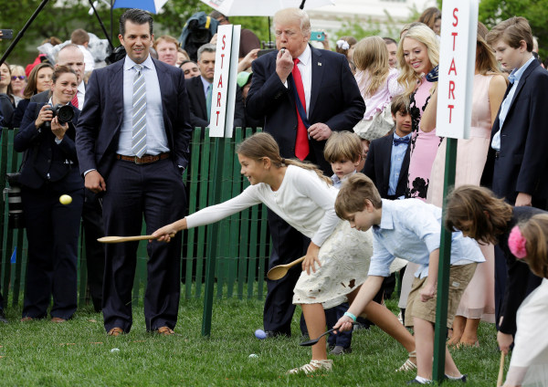 Image: U.S. President Donald Trump and his son Donald Trump, Jr., watch children roll Easter Eggs at 139th annual White House Easter Egg Roll