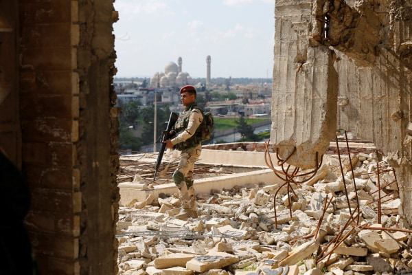 Image: A member of the Iraqi security forces stands guard as Ameen Mukdad, a Mosuli violinist, performs in eastern Mosul