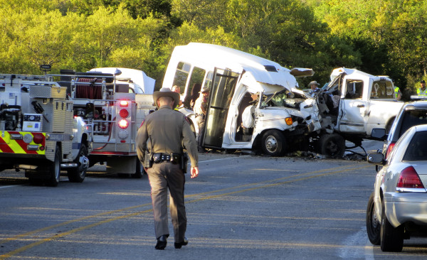 Image: Authorities investigate the scene after a deadly crash involving a van carrying church members and a pickup truck