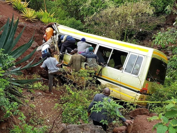 Image: Residents attempt to rescue survivors at the scene of an accident that killed schoolchildren, teachers and a minibus driver along the Arusha-Karatu highway in Tanzania's northern region of Arusha