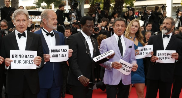"Image: The cast of The Expendables 3 hold up banners reading ""Bring Back our Girls"""