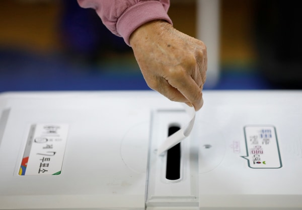 Image: A woman casts her vote at a polling station in Seoul