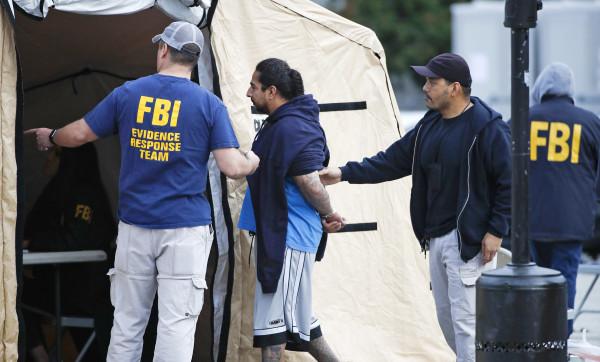 Image: A man is taken into custody by FBI agents
