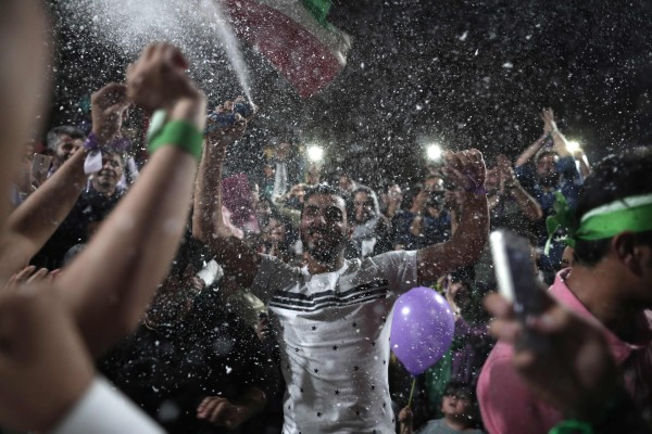 Image: Supporters of newly re-elected Iranian President Hassan Rouhani dance during a gathering to celebrate his victory