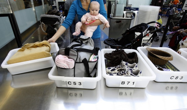 Image: A Passenger Holding her baby prepares to go through a security checkpoint at Los Angeles International Airport
