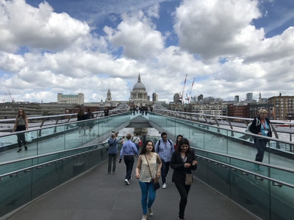 Image: Londoners and tourists walk across the city's Millennium Bridge