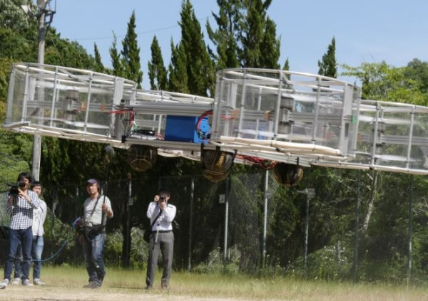 Journalists film Cartivator's flying car during its demonstration in Toyota
