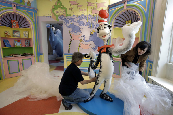 Image: John Simpson, left, project director of exhibitions for The Amazing World of Dr. Seuss Museum, and his wife Kay Simpson unwrap a statue